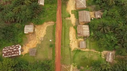 Aerial view of houses by dirt road, surrounded by trees in Kribi in Cameroon, west Africa. Dronees forward along the road.