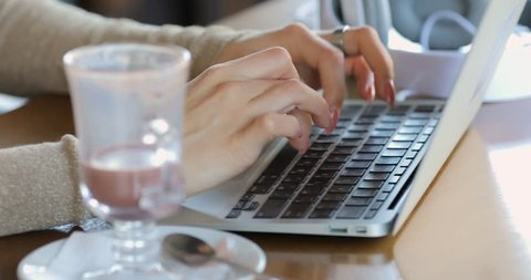 Young woman blogger working by laptop in cafe closeup, typing description  for her video