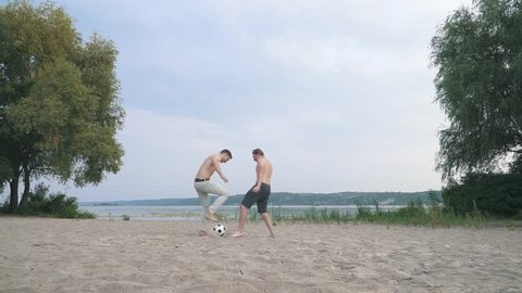Two young guys playing football Competition between people Friends have a fun together Spending time outdoors Active lifestyle