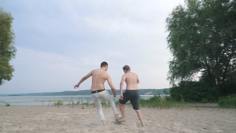 Two young boys playing football at the river Competition between people Young man is scores Friends have a fun together Spending time outdoors Active lifestyle