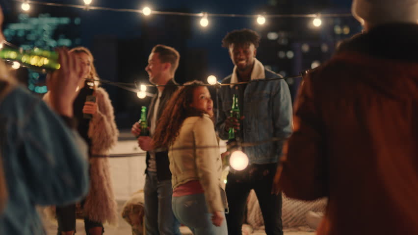 Happy multiracial friends having fun dancing playfully together enjoying rooftop party at night laughing celebrating friendship | Shutterstock HD Video #1020249418