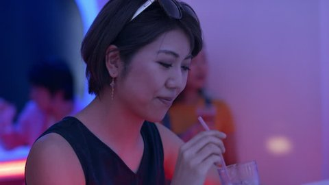 Japanese woman sitting with a cocktail and drinking it through a straw in a funky, cool bar with soft interior lighting. Close up shot on 4k RED camera.