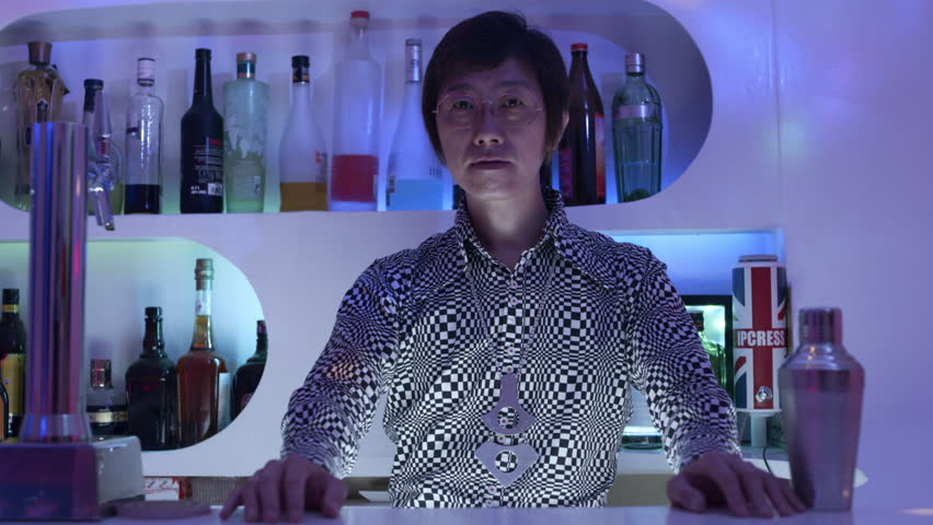 Portrait of a Japanese bartender with 70s shirt standing behind the bar in a cool, funky bar with soft interior lighting. Medium shot on 4k RED camera.