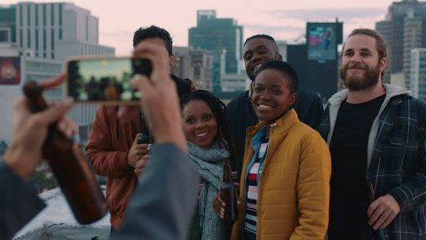 diverse group of friends posing for photo enjoying rooftop party celebration having fun drinking alcohol sharing weekend in city on social media
