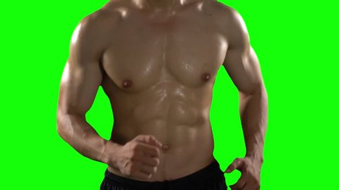Unrecognizable young man with muscular body doing exercise by running in place with green screen background