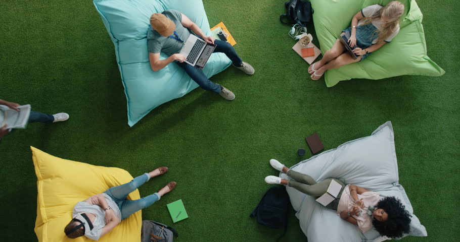 Young diverse business students working on business project exam sharing ideas relaxing in vibrant modern recreational workplace top view | Shutterstock HD Video #1020333298