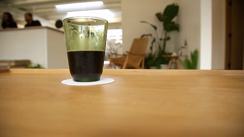 A mans hand lifts up a glass of dark beer and sets it back down.