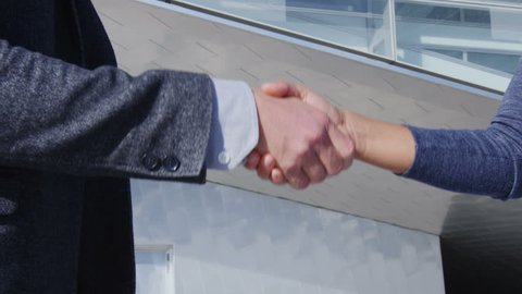 Business Handshake - business people meeting shaking hands. Handshake between business man and woman outdoors by office building. Business suits, young people shaking hands closeup. SLOW MOTION
