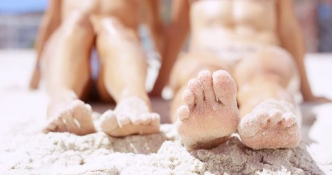 Close up of sandy feet wiggling toes two beautiful young woman sitting on tropical beach vacation