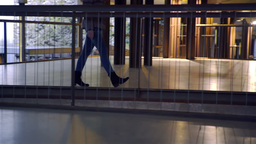 Female legs walk over iron bridge underground HD. Low angle close up of person walk in underground museum with iron floor, walking pass the camera.