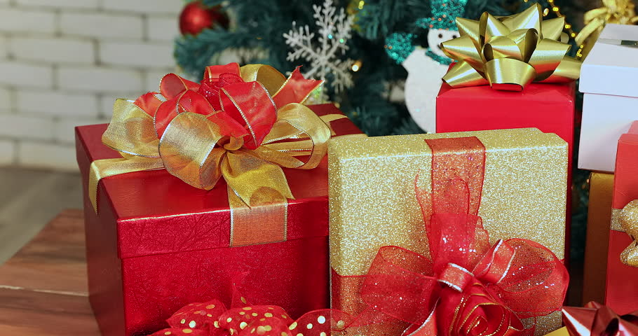 Close up scene VDO of beautiful gift boxes , then camera pan around it, Christmas tree behind it, concept for or Christmas celebration.  | Shutterstock HD Video #1020435778