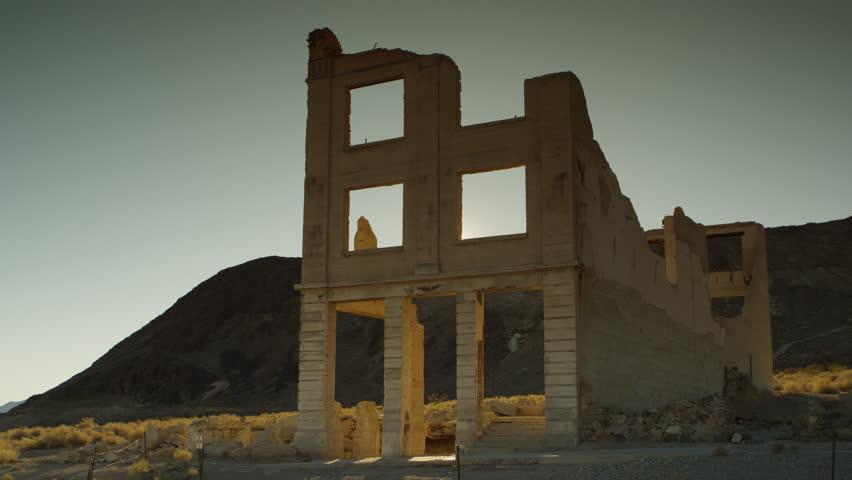 The Setting Desert Sun Peeks through an Upper Window of the Famous Cook Bank Ruins in Rhyolite, Nevada. (Sun Event begins at :06 sec) | Shutterstock HD Video #1020436168