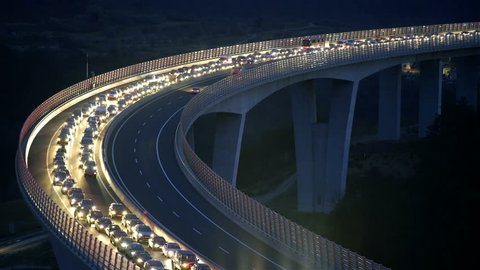 Long shiny line of vehicles on highway HD. Night time shot of highway with one side full of vehicles standing, others with few cars driving red tail lights shining.