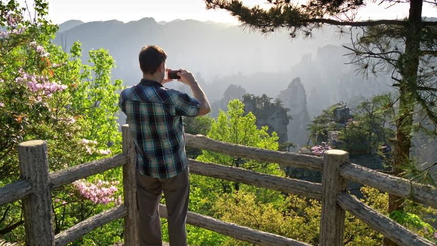 A tourist making snapshots of scenic views of vertical cliffs in Wulingyuan with his smartphone during a bright sunny day. Zhangjiajie, China. UHD #1020459208