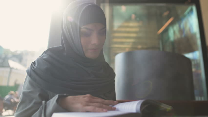 Motivated Muslim female student reading book in cafe modern education literature | Shutterstock HD Video #1020512068