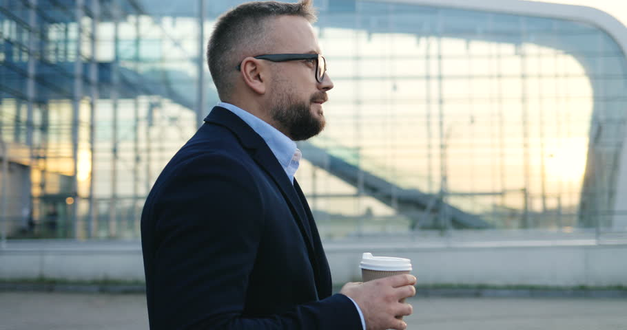 Side view on the Caucasian handsome businessman in glasses walking outside big glass urban building of airport, drinking coffee and turning his head to the camera. Close up. #1020518878