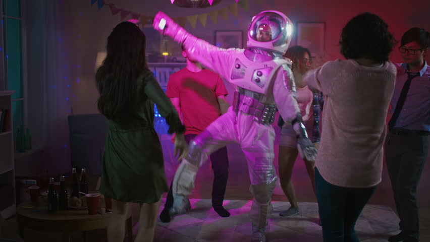 At the College House Costume Party: Fun Guy Wearing Space Suit Dances Off, Doing Robot Dance Modern Moves. With Him Beautiful Girls and Boys Dancing in Neon Lights. | Shutterstock HD Video #1020543028