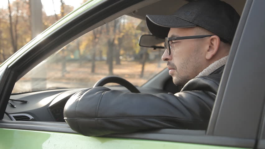 A private detective or a spy conducts surveillance of the object of surveillance. A man secretly taking pictures from the car window | Shutterstock HD Video #1020566698