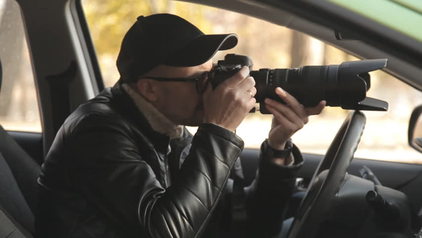 A private detective or a spy conducts surveillance of the object of surveillance. A man secretly taking pictures from the car window | Shutterstock HD Video #1020566728
