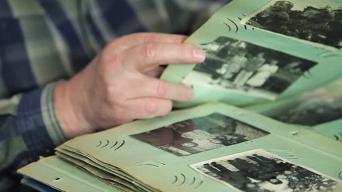 Lviv \ Ukraine - July 7 2018: Hand elderly man viewing their old photos of the house family senior memory photo picture aged album caucasian retired married marriage grandparent age looking past close