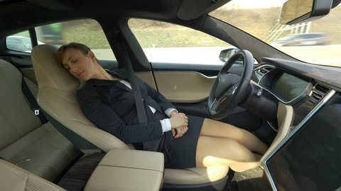 CLOSE UP: Carefree Caucasian woman in a suit jacket and skirt sleeping in a high tech autonomous car driving itself down the freeway. Relaxed businesswoman dozes off while her car drives her to work.