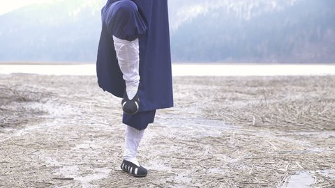 851b1e669 Kung Fu Martial Arts Master standing on one leg close up HD. Low angle dolly