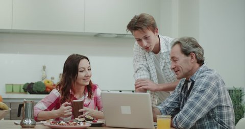 Mature charismatic family on the dinner table spending time while eating , looking through the laptop and have a interesting conversation parents between their son.