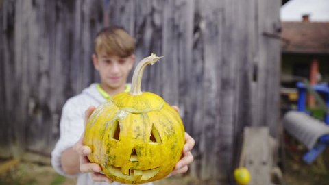 Boy holding up pumpkin head face close up HD. Young creative boy show off cut out face on pumpkin head holding in front of him in focus. Boy in sweater in front of barn blurred in background.