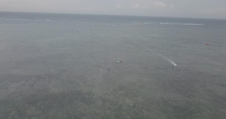 Extreme sport kitesurfing in tropical blue ocean, clear beach. Aerial  | Shutterstock HD Video #1020707038