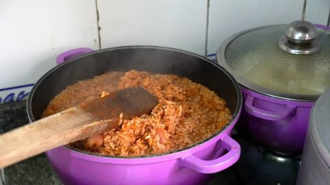 African woman preparing a pot of Nigerian Jollof rice with a wooden spoon