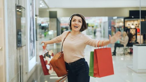 Happy female shopaholic is having fun in shopping mall listening to music in headphones, dancing with bright bags and laughing pointing at goods in shop windows.