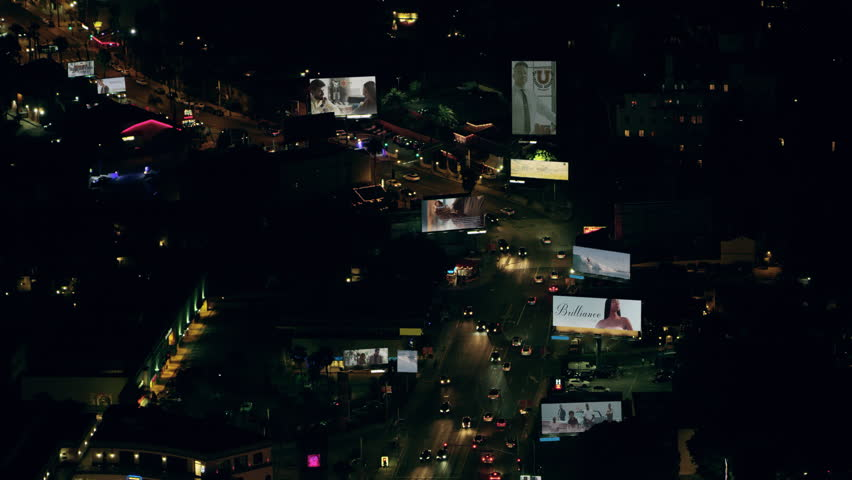 Aerial view of city traffic on Sunset Boulevard with billboards with fake advertisements on a clear night in Los Angeles, California. Shot on 4K RED camera.