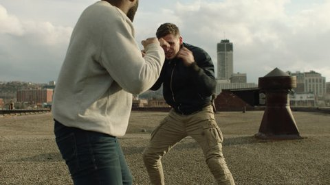 Buff fighter man punches and knocks out another man on a warehouse rooftop in overcast sunlight. Medium shot in 4K with an Alexa Mini camera
