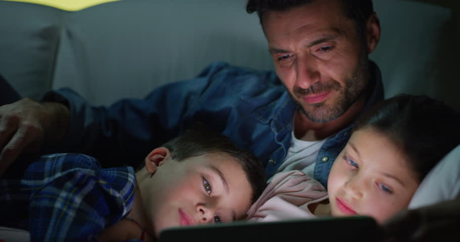Portrait of happy father and kids using a tablet on sofa in the evening in slow motion. Shot with RED camera in 8K. Concept of family entertainment, education, technology