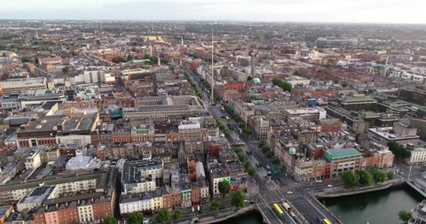 The drone is tracking backwards facing the spire and O'Connell street flying across the river Liffey and Grafton street