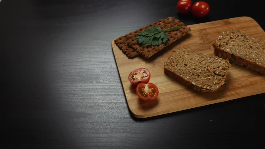 Healthy breakfast. Fresh grain bread,  ripe cherry tomatoes and bread crips with parsley on the cutting board. Camera moves from left to right | Shutterstock HD Video #1020868588