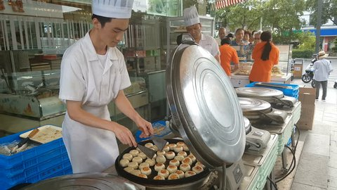 SUZHOU, CHINA - SEPTEMBER 2018: Chefs wearing white uniforms prepare traditional mooncakes, a popular food (desert) for the Mid-Autumn festival celebrations in Suzhou, China