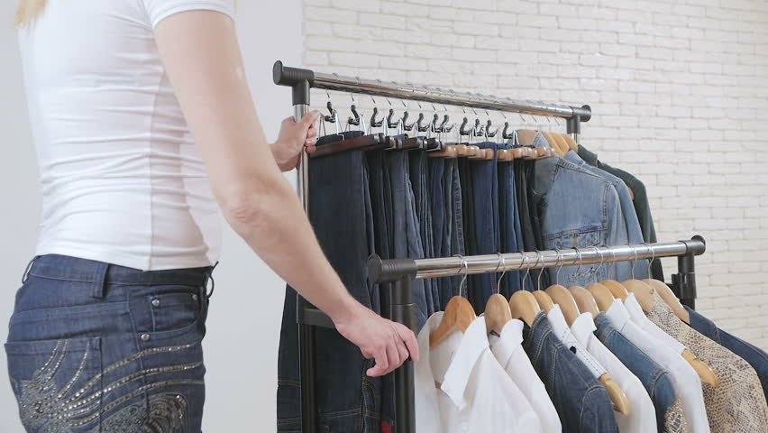 Woman moves shelving with clothes in the store   Shutterstock HD Video #1020896158