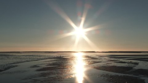 Sun shines over the ocean on beautiful sandy beach with waves crashing, no people in sight.