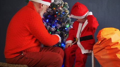 Happy child Dressed in Santa Claus costume, pulls yellow pig toy out of gift box. father in Santa Claus hat helps him against background of Christmas tree in garlands. Symbol of  chinese new year