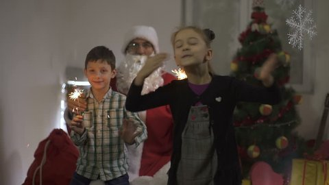 Female child sending kisses towards the camera like greetings and best wishes for new year, in background Santa Claus and little boy with bengal lights, decorated Christmas tree and gifts, slow motion