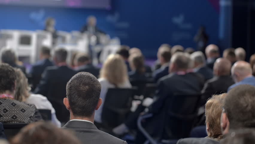 Politician or manager at public company forum. Listeners or spectators view show at large room or crowded economic center on row of chairs. Professional development of information occupation for sale | Shutterstock HD Video #1020954658
