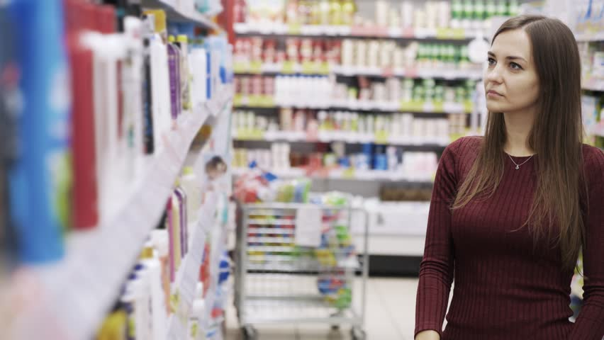 Beautiful woman looking at cosmetics in supermarket. Attractive girl buying cosmetic product. Housewife takes goods from shelf, sniffs and puts it back. Concept advertise business, consumerism, beauty