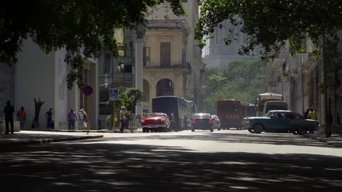 iconic old 1950's vintage classic american car taxi driving on famous alley street in old neighborhood Havana, Cuba