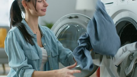 Close Up of a Beautiful Young Woman in Homely Clothes Sitting in Front of a Washing Machine. She Loads the Washer with Dirty Laundry. Bright and Spacious Living Room with Modern Interior.
