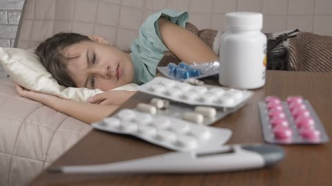 Ill girl lying on bed. Girl feeling bad and looking at stack of pills on table.