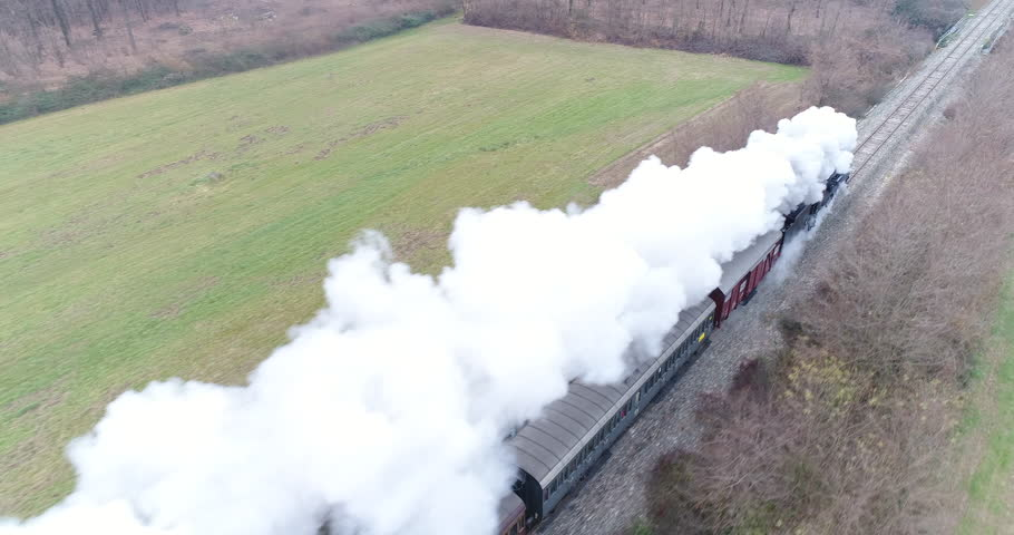Old train: aerial view of steam train running on the tracks in the countryside. Heritage historic steam locomotive with white smoke seen from above by drone.