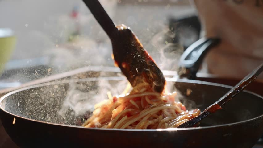 Cooking and stirring the spaghetti with red tomato sauce in the frying pan, close-up in slow motion | Shutterstock HD Video #1021204648