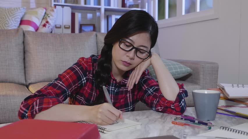 slow motion tired concentrated woman hard working at home in midnight. college girl preparing for exam study at night stay up late. student puts hand on chin on table with full of text books around.