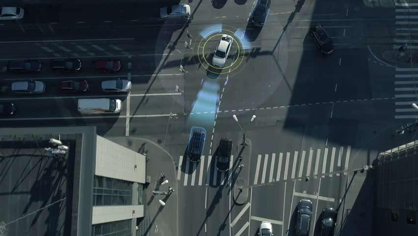Top Down Aerial Drone: White Autonomous Self Driving Car Moving Through City. Concept: Artificial Intelligence Scans Surrounding Environment, Detecting Cars, Avoids Traffic Jams and Drives Safely. | Shutterstock HD Video #1021307818